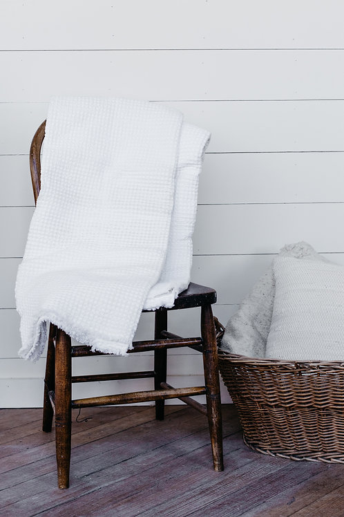 Light and airy waffle throw blanket draped over a farmhouse chair. Sold by Salt Creek Mercantile.