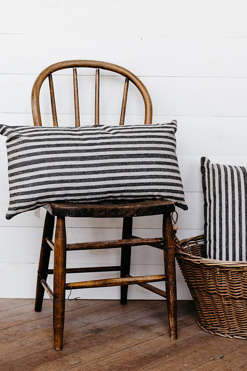 Cozy striped lumbar pillow displayed on a wooden farmhouse chair. Sold by Salt Creek Mercantile.