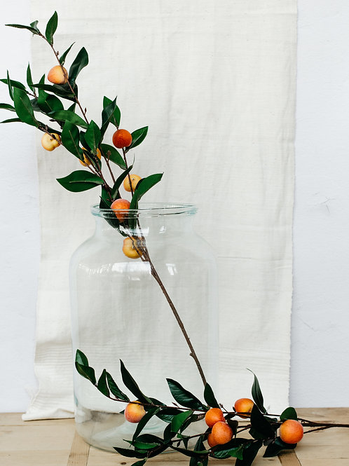 Artificial peach fruit branch displayed in large glass vase. Sold by Salt Creek Mercantile.