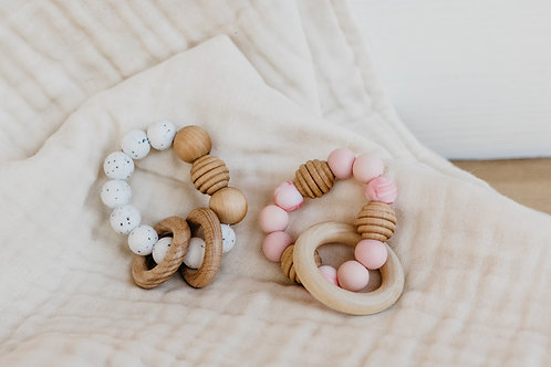 White speckled and pink wood and silicone teething ring, sold by Salt Creek Mercantile.