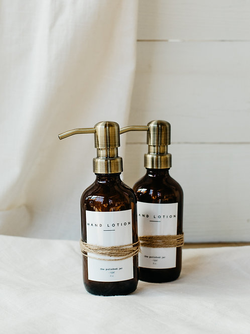 2 amber glass lotion jars with brushed brass pumps. Sold by Salt Creek Mercantile.