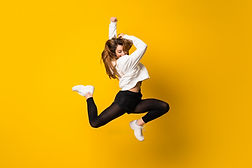 young-woman-jumping-isolated-yellow-wall