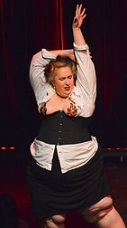 Woman in white shirt and black corset doing burlesque dance