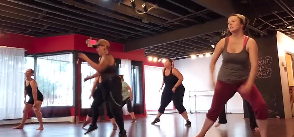 Video of students doing a pilates workout on mats in a dance studio.