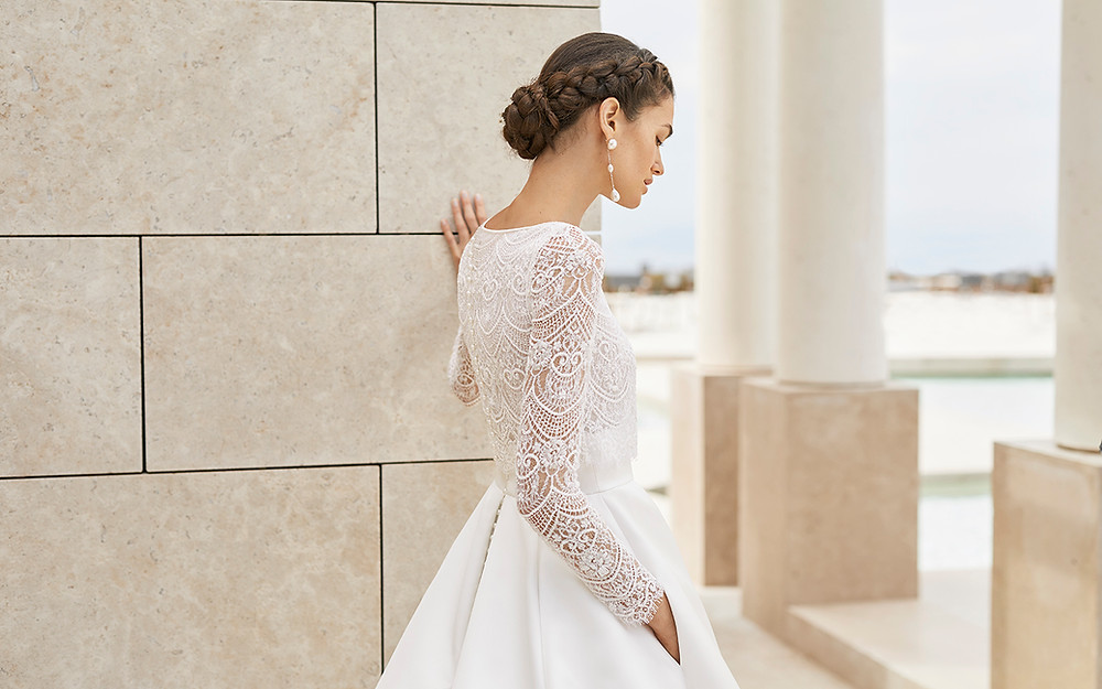 Picture yourself walking into ballroom wearing the Sandy Gown and being greeted by all your loved ones. A sophisticated ceremony will be the ideal backdrop for such a standout wedding dress. A princess cut and an exquisite tailored design are what dreams are made of. Modern brides will love the royal satin craftsmanship, enhanced with beaded lace and intricate embroidered detailing. Long sleeves add even more romance whilst a bateau neckline keeps the look classy and timeless. A pleated waistline allows this sensational skirt to drape beautifully. The charming combination of royal satin and lace create a truly wonderful wedding dress for a classic bride. Handy pockets complete the look.