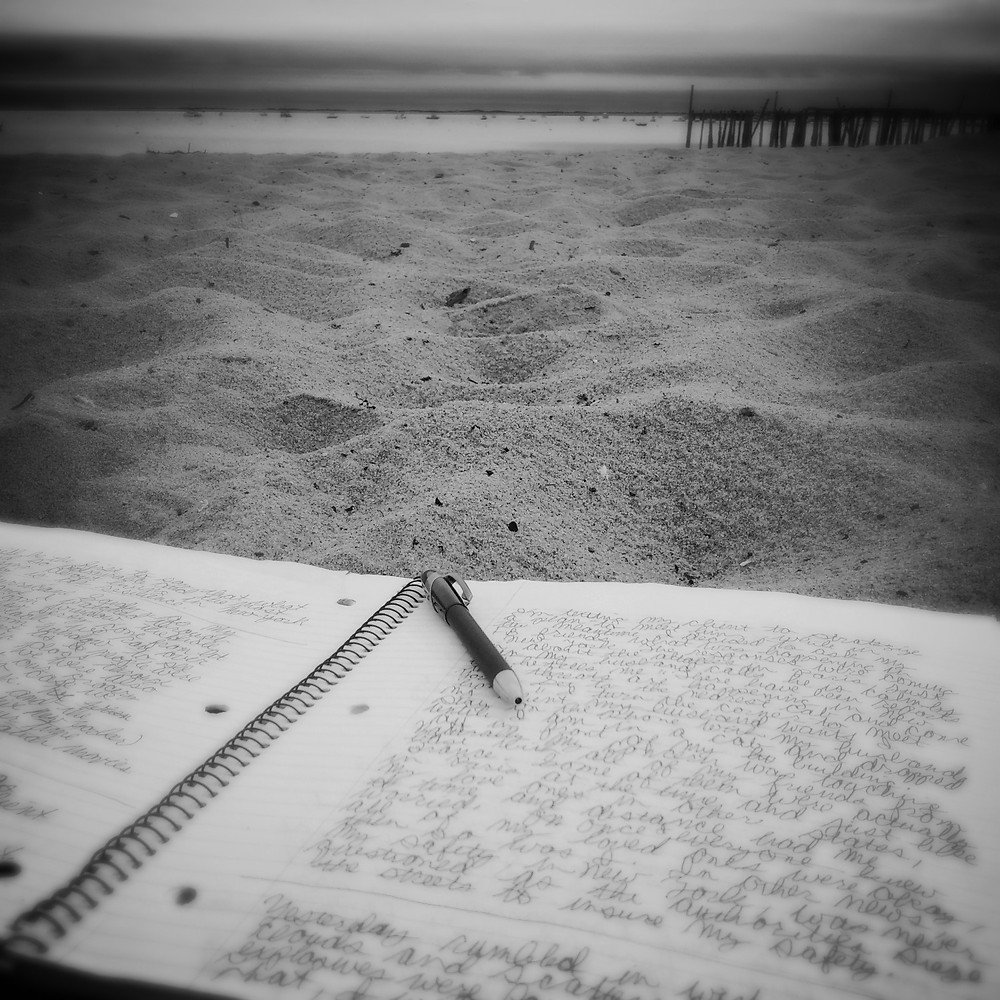 Notebook journal on the beach with sand