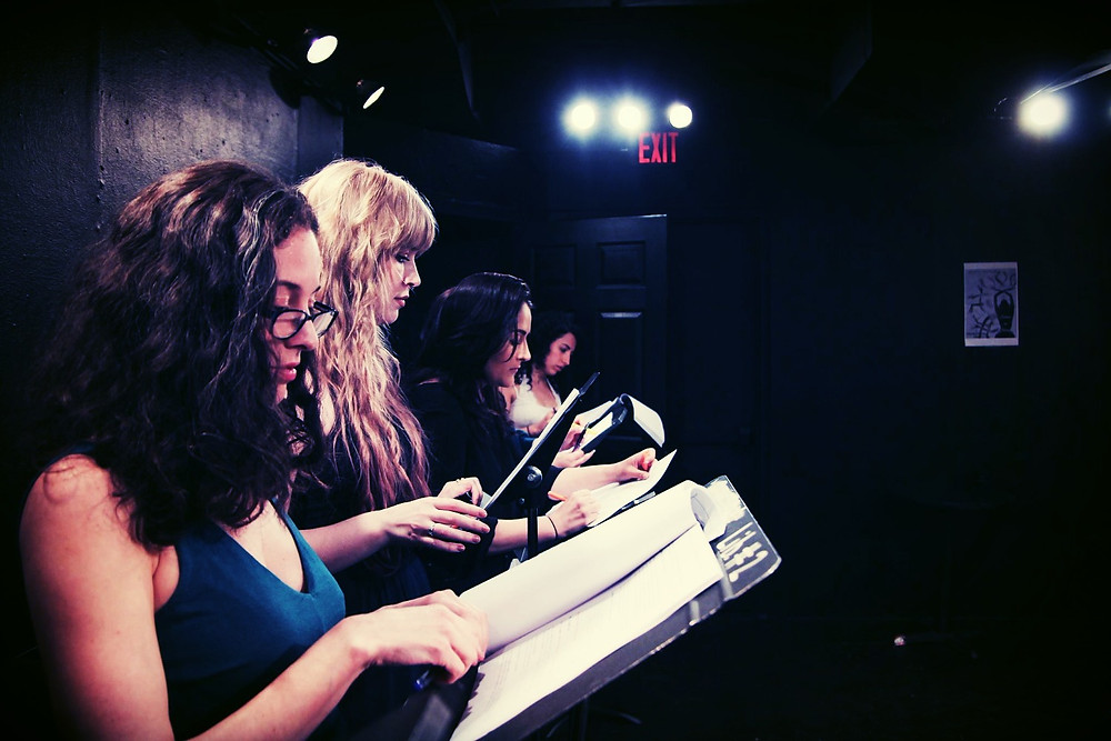 Four women performing a table read with scripts on stage