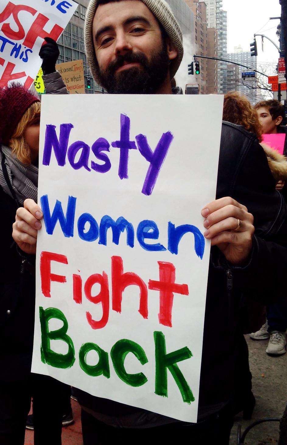Man holding sign Nasty Women Fight Back
