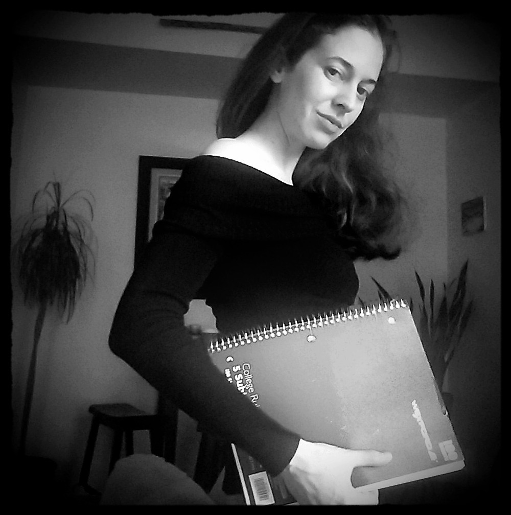 Woman  in black dress, holding blue notebook