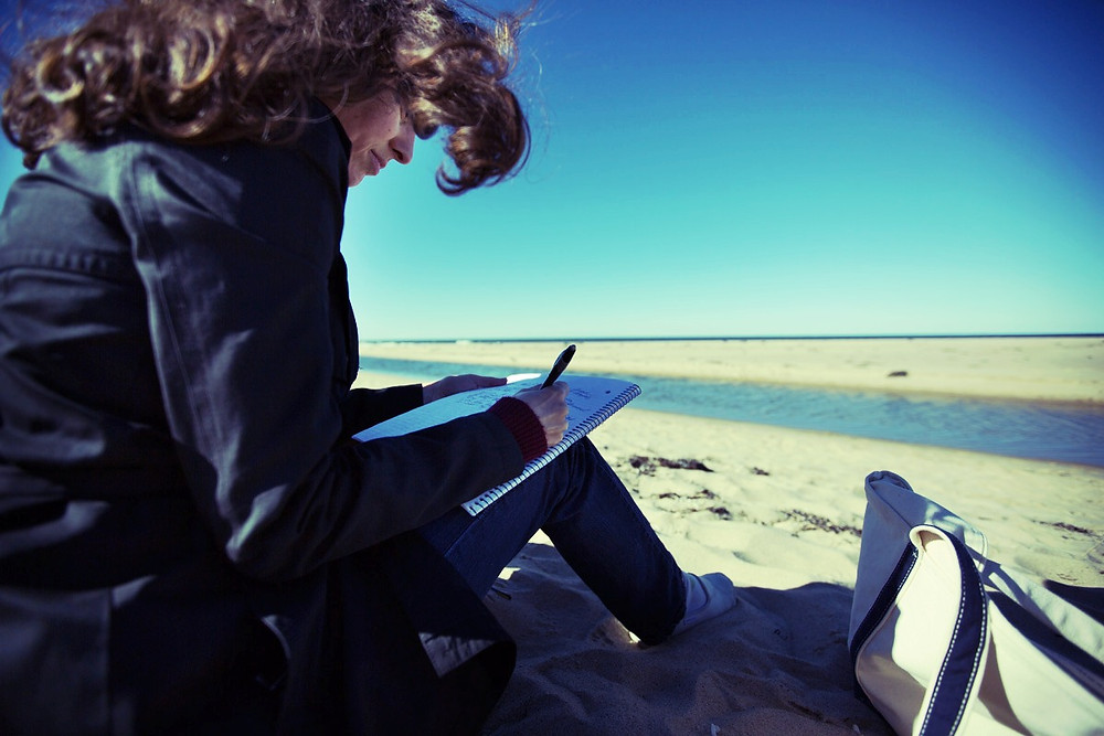 Woman on Race Point Beach in Provincetown Massachusetts sitting on the sand writing