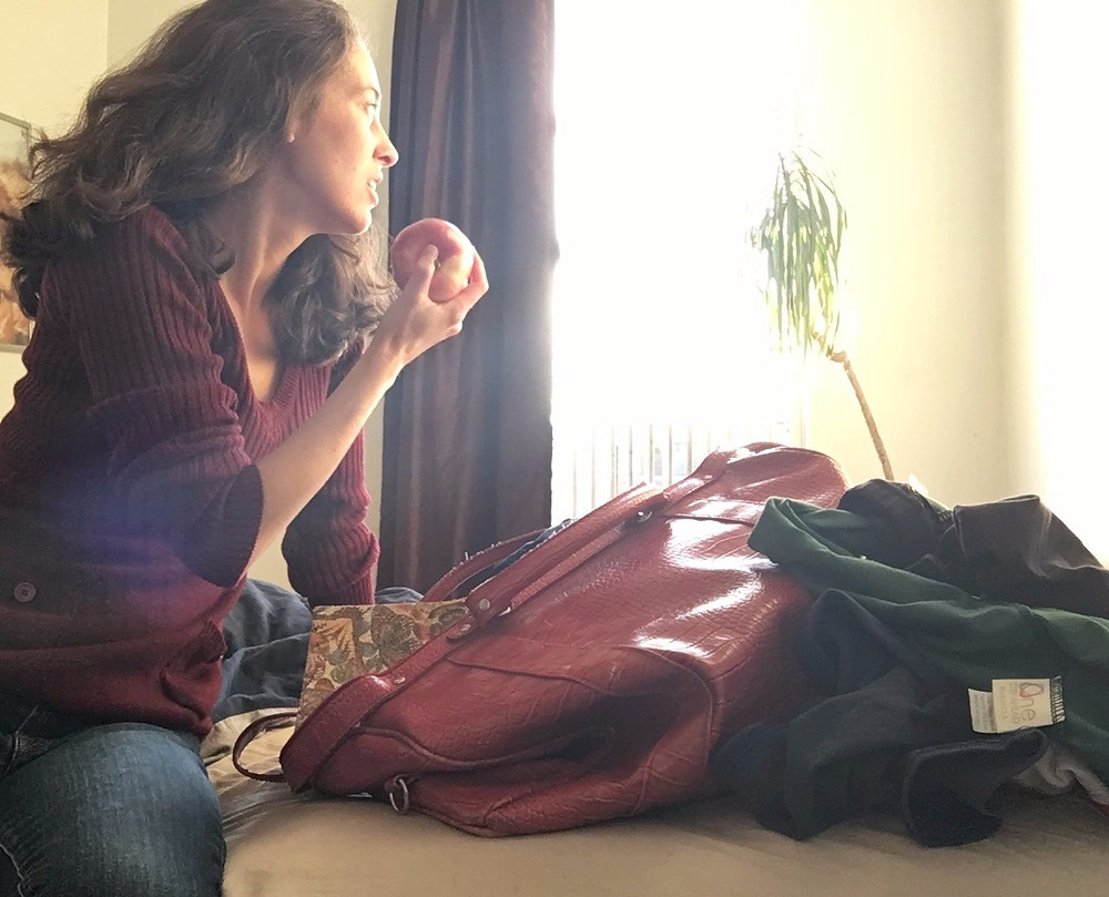 A Woman sitting on bed eating apple next to bag