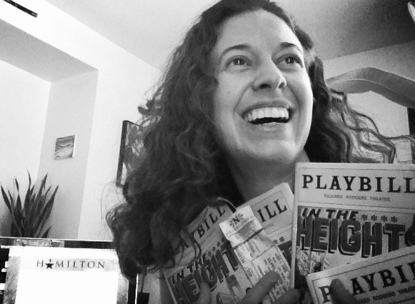 "Woman holding a handful of ""In the Heights"" playbills while looking at Hamilton lottery"