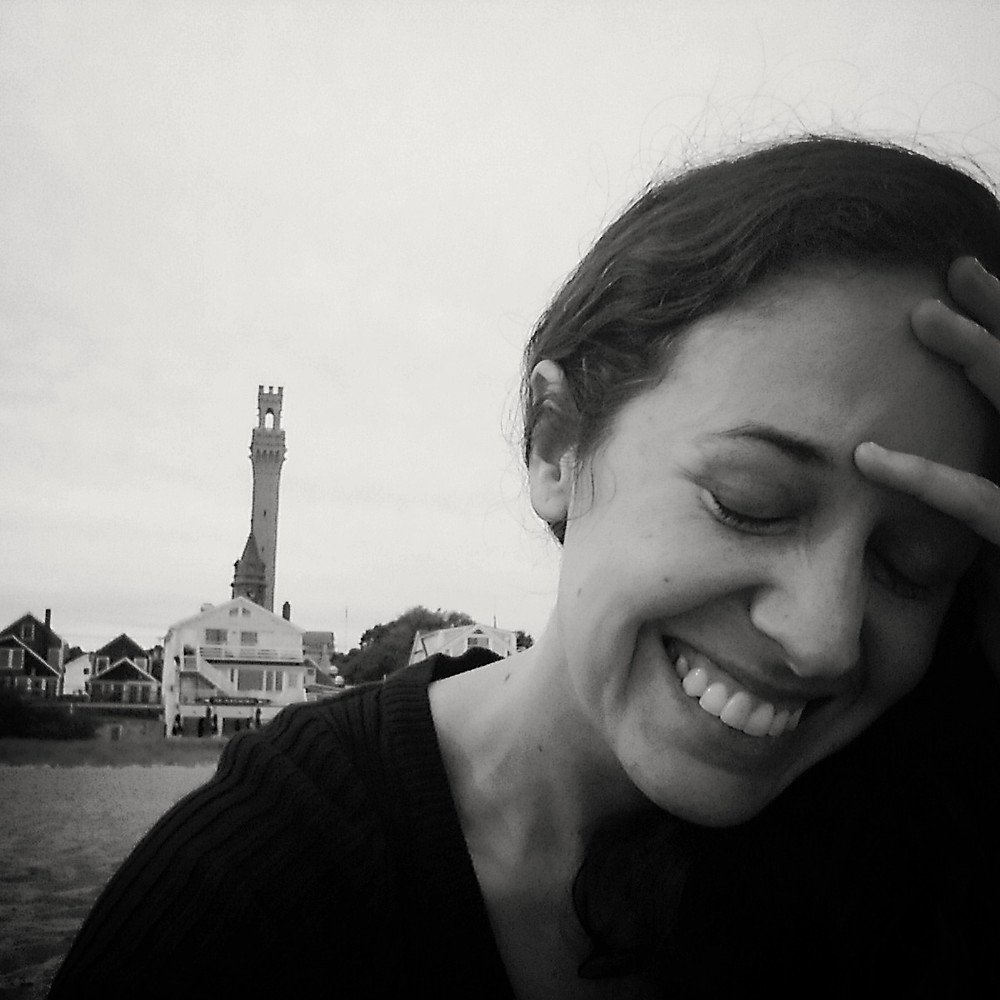 Woman smiling on beach Pilgrim's Monument view in Provincetown Massachusetts