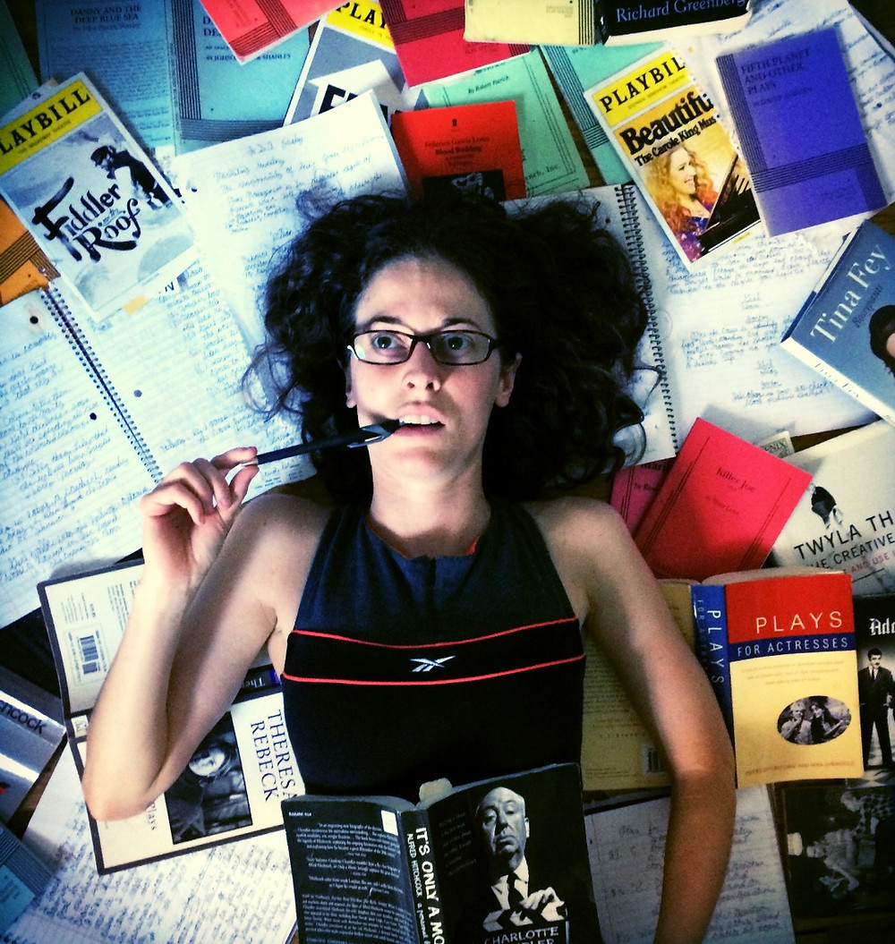 girl lying in pile of plays,books,notebooks and playbills
