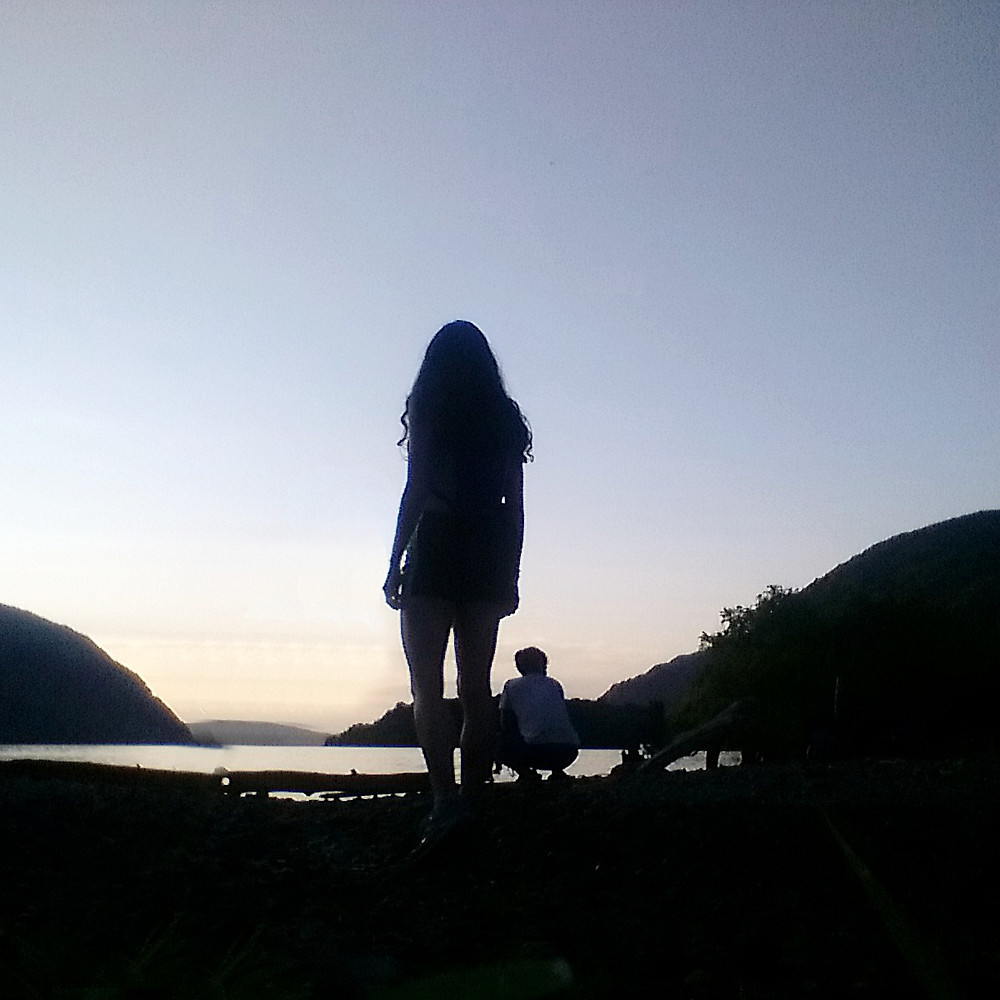 Girl looking at the hills on a lake during sun down