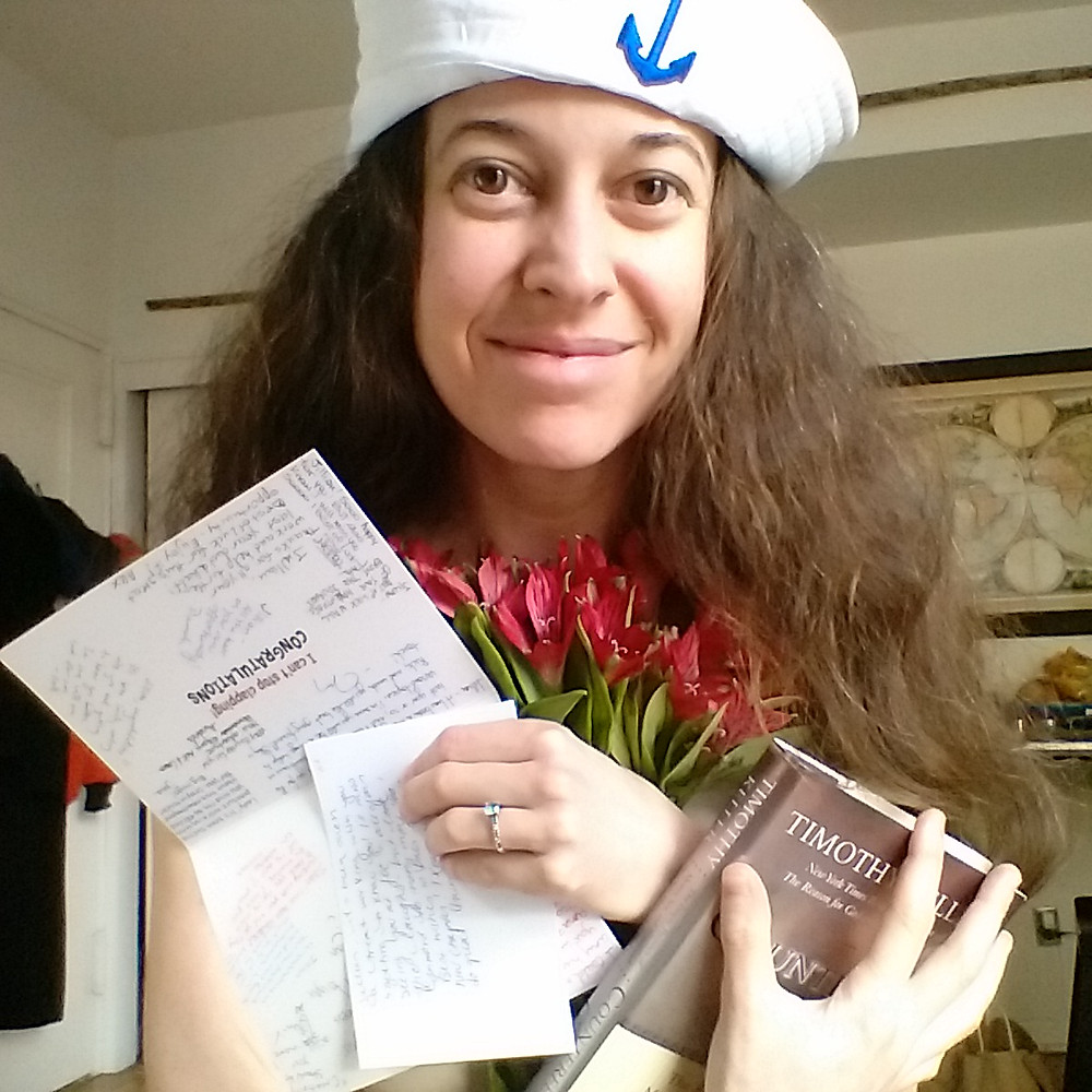 Woman in sailor hat holding thank you card and book