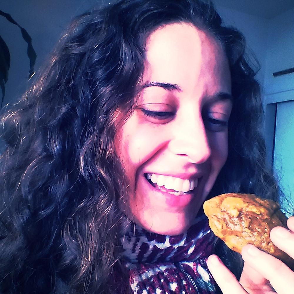 Girl biting into a pumpkin cookie