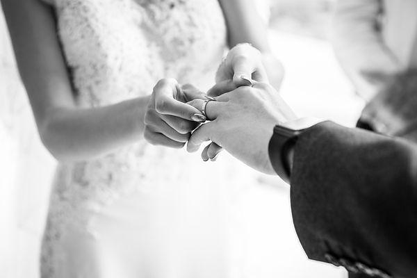 lady putting wedding ring onto partner during their wedding day