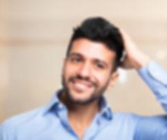 man touching full head of hair followig hair growth treatment.