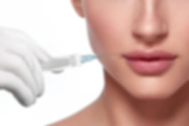 Model posing with dermal filler syringe near lips and showing off newly defined lips post injection
