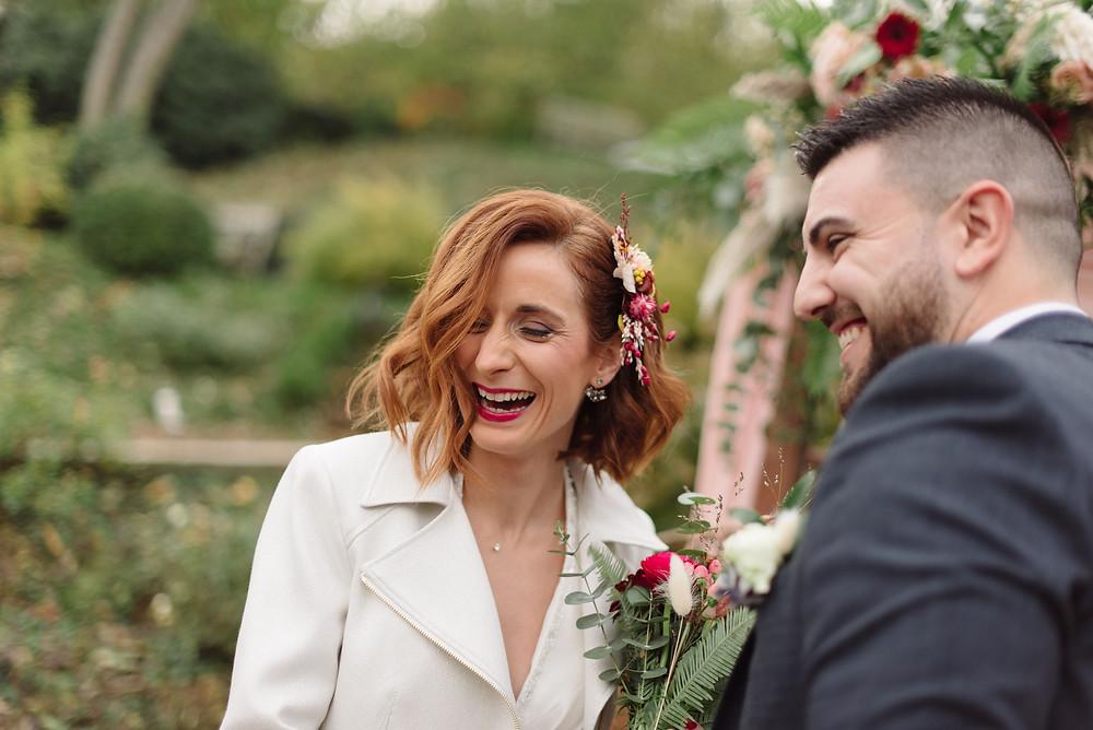 Couple en plein fou rire lors de leur cérémonie de mariage laïque devant une arche fleurie