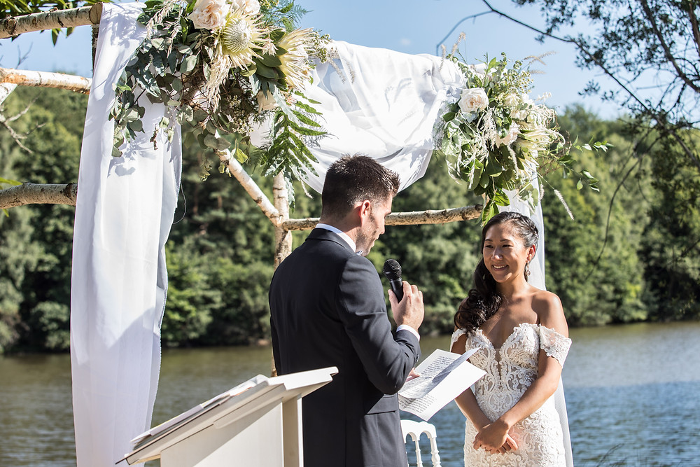 Bilingual ceremony, groom and bride couple exchanging vows in front of their arch next to a lake