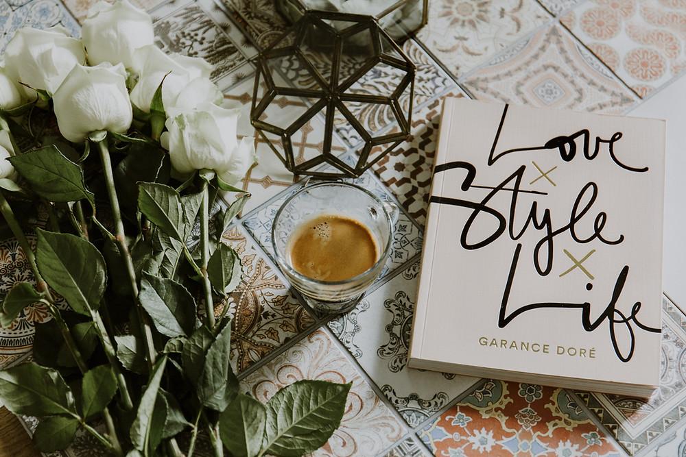 """Livre """"Love Style Life"""" de Garance Dore à coté de fleurs et d'une tasse de café, le tout posé sur des carreaux de ciment colorés"""