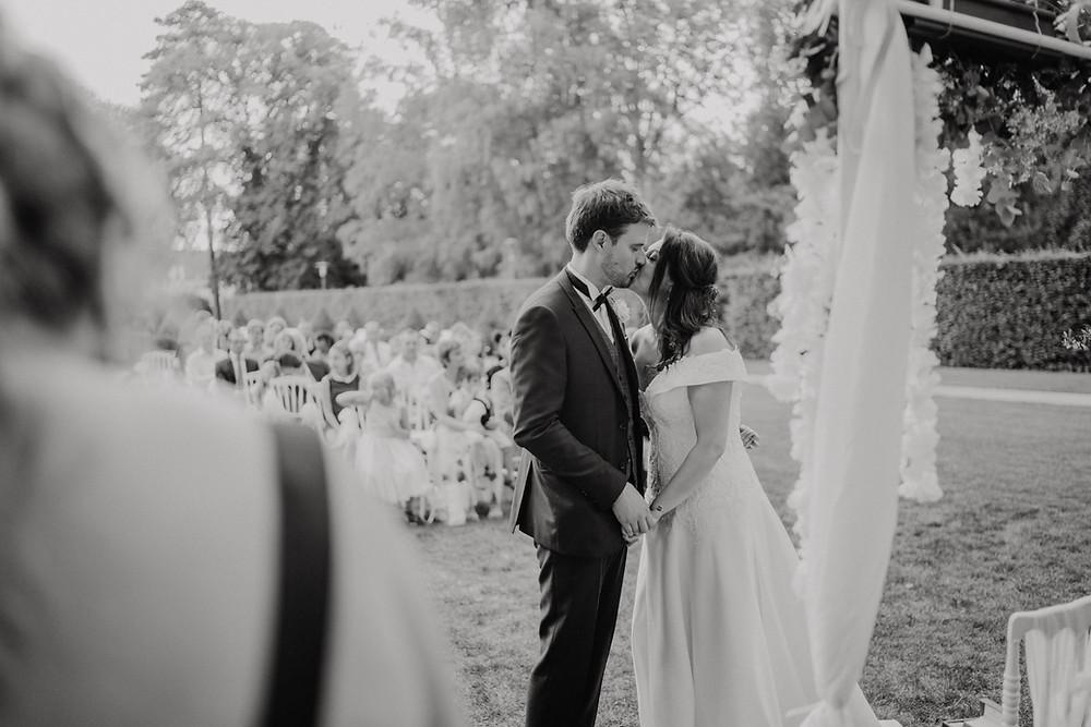 Couple de mariés en train d'échanger leurs vœux devant le kiosque fleuri