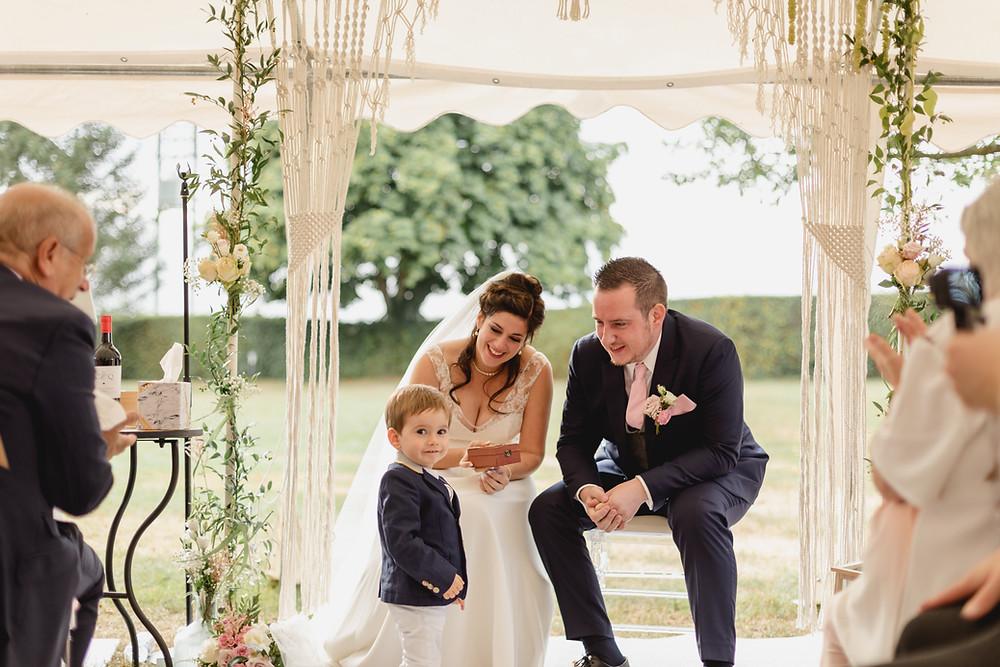 Couple de mariés avec leur petit garçon assis devant l'arche fleuri tenant les alliances