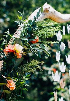 Arche en bois flotté fleuri lors d'une cérémonie laïque avec des origamis