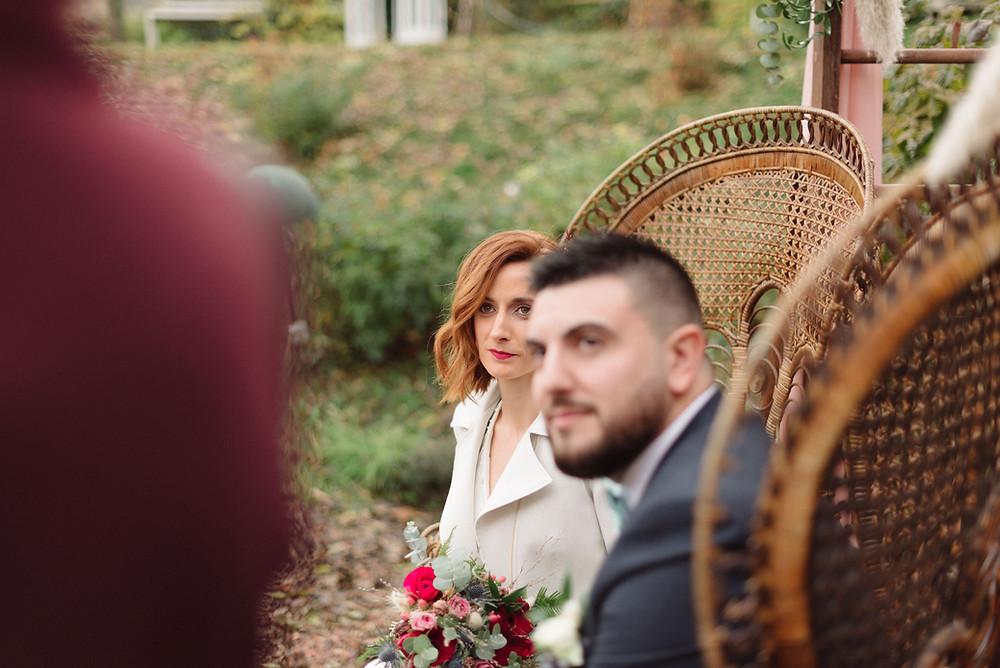 Un couple de mariés lors de la cérémonie laïque en extérieur de leur mariage qui regardent leur officiante