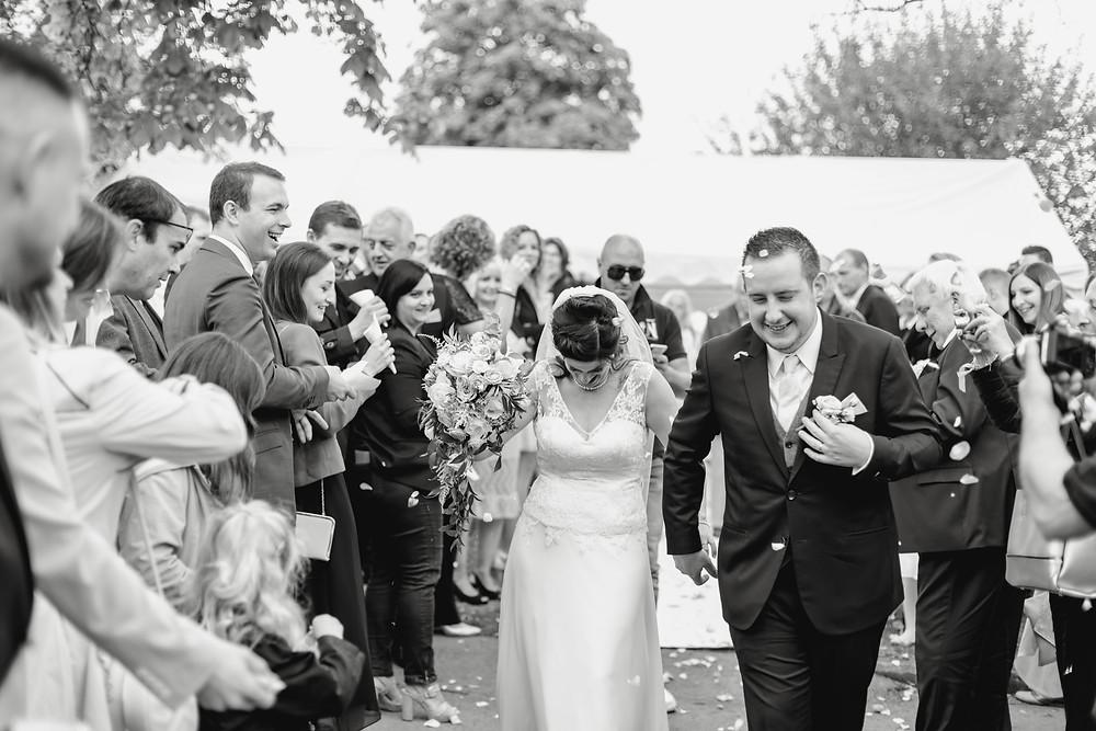Les mariés en sortie de cérémonie laïque sous les pétales de fleurs des invités