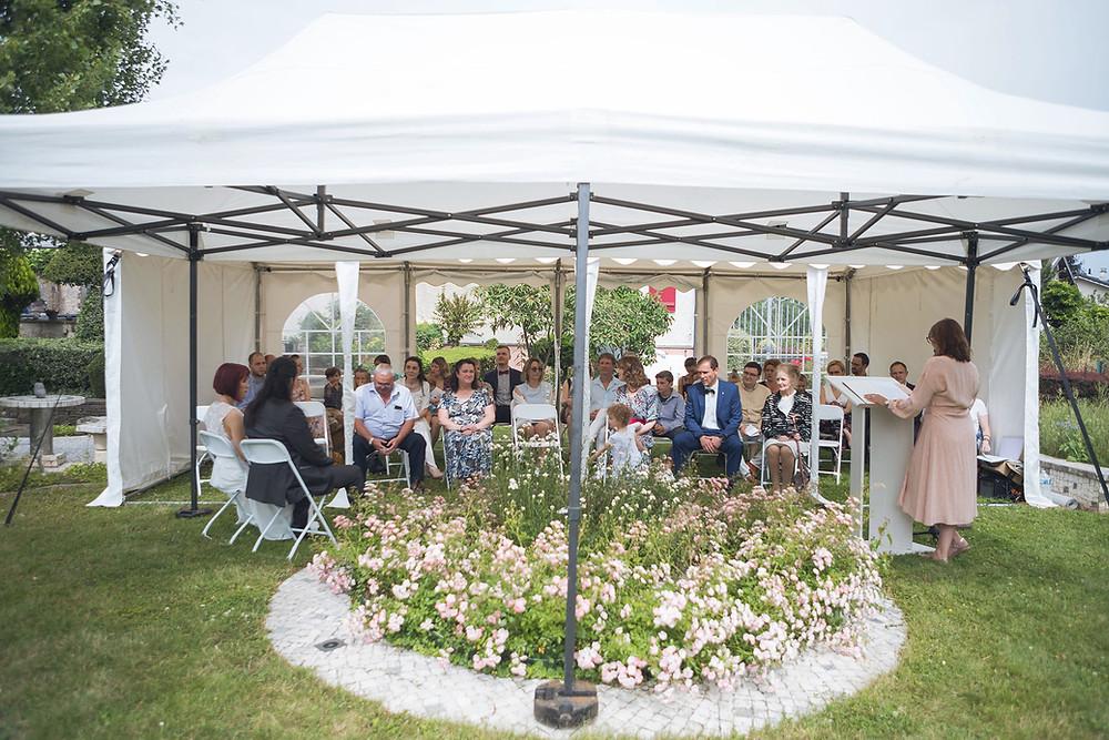 Couple de mariés avec leur officiante de cérémonie laïque intime dans leur jardin à la maison