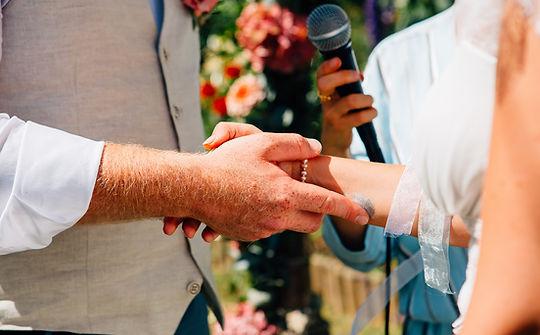Couple se tenant la main pendant leur cérémonie laïque de mariage