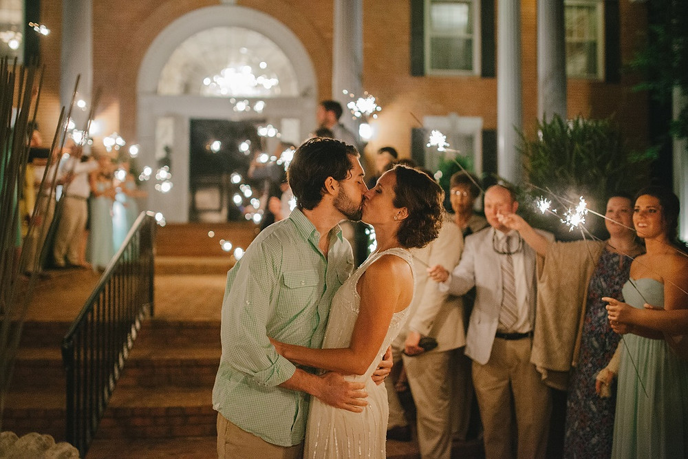 Couple en train de s'embrasser à la fin de la cérémonie de mariage avec les invités qui font scintiller des étincelles