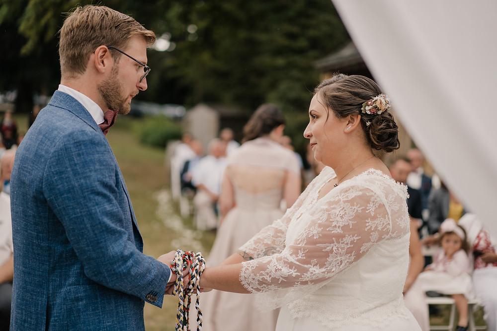 Couple de marié avec leur officiante de cérémonie laïque devant une arche fleurie
