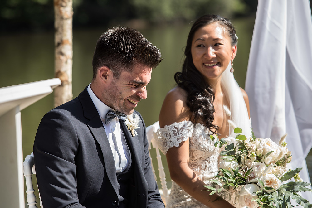 Groom and bride laughing during their wedding ceremony in the south of France American Chinese wedding