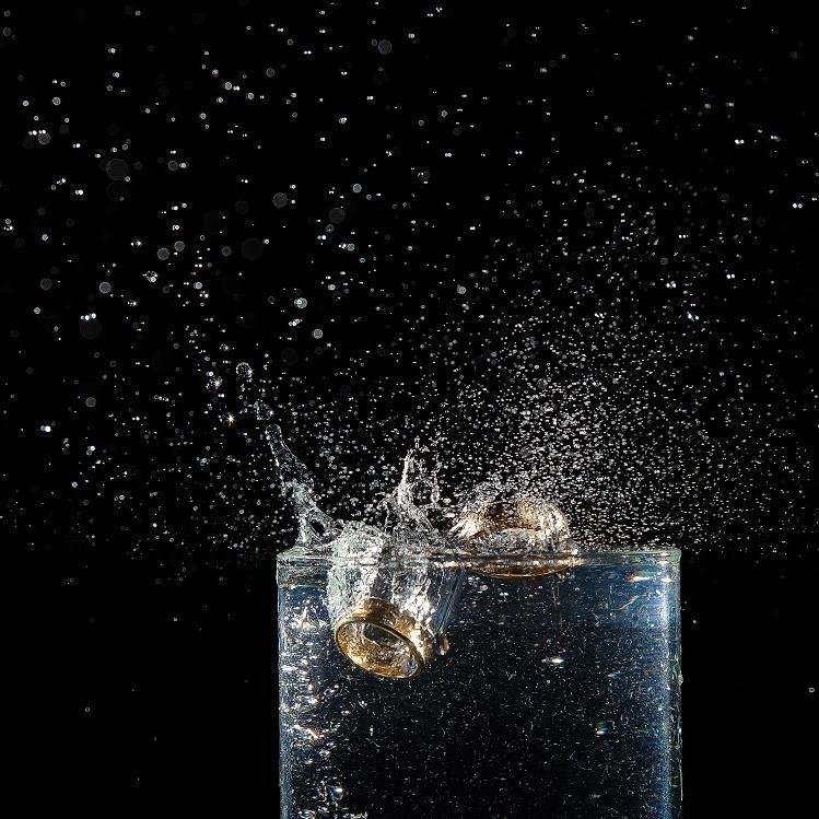 Deux alliances tombant dans un verre d'eau en éclaboussant sur fond noir