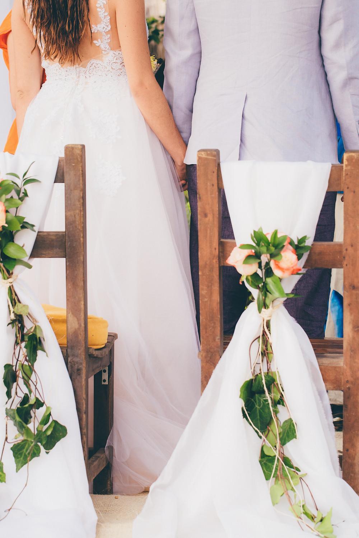 Couple de mariés vu de dos se tenant la main pendant la cérémonie laïque de leur mariage