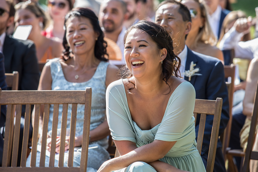 Photo of the guest laughing during the wedding ceremony