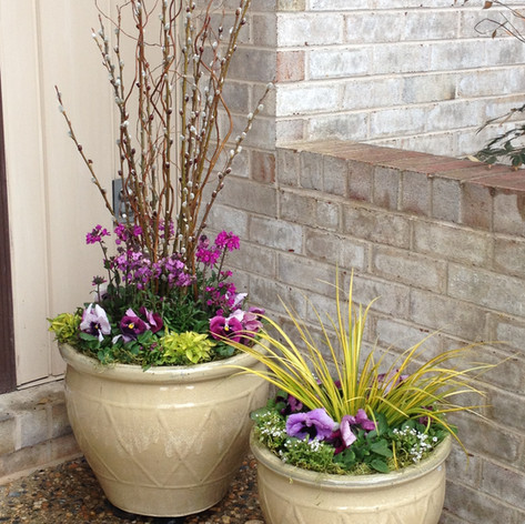 two potted spring container plants decorating a front porch