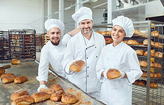 Bakers smiling holding fresh bread in th