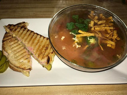 A panini pressed Cuban Sandwich , with homemade Chicken tortilla Soup