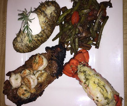 Grilled Steak topped with Shrimp marinated in a rosemary butter and lemon a Parmesan crusted lobster