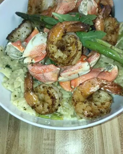 Blackened Shrimp and Jonah Crab claws with a sautéed onion and Asparagus Pesto Alfredo sauce tossed