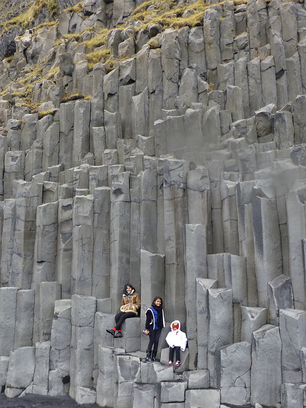 Three sisters stand against a surreal landscape of hexagonal rock formation in Vík, Iceland