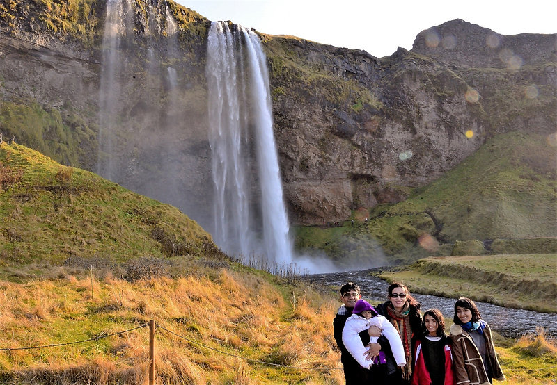 A family traveling to Iceland with their kids are standing in front of the unique Seljalandsfoss waterfall in Iceland