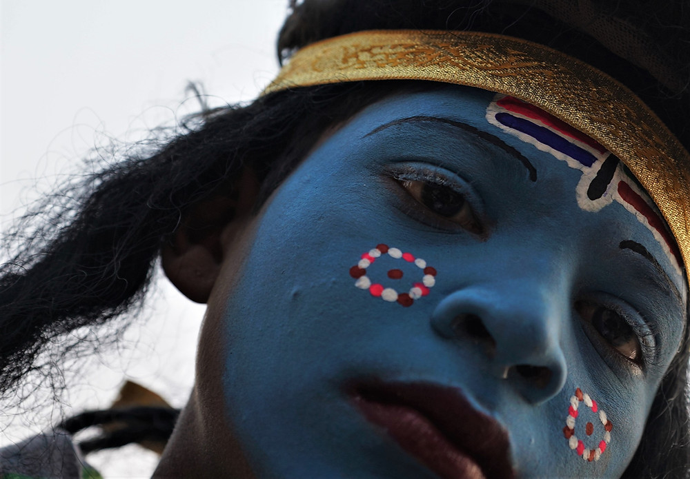 A little girl in Varanasi's Dashashwamedh Ghat wearing blue paint and intricate head-dress.