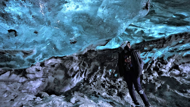 A girl stands inside an Icelandic ice cave illuminated by the diffused and refracted blue light entering through the cave roofs