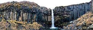 Svartifoss waterfall in Iceland falling over the stony corrugated cliff in a strange landscape